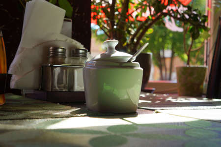 Breakfast by window at sunny morning. Sugar bowl on table. Selective focus.