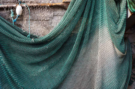 Green fishing net hanging on a wall for drying. Banque d'images