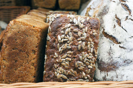 Loaf of rye bread with sunflower seeds in wicker basket. Banque d'images