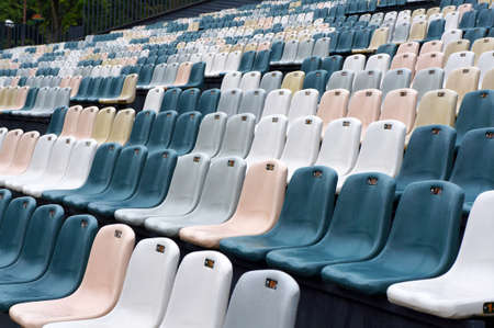 Blue and white seats in rows in empty auditorium outdoors wet with  water drops after rain.