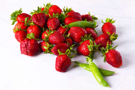 Fresh ripe juicy red strawberries and pods of green peas on white marble table.