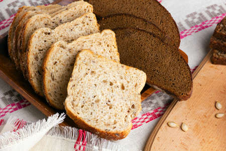 Slices of wheat bread baked with seeds and rye bread.