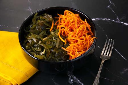 Sea kale Laminaria and carrot salad in black bowl.