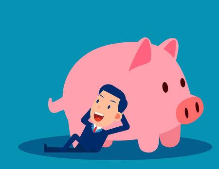 A businessman reclines close to the piggy bank. Saving money concept