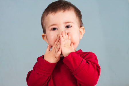 covering the face: Little child covers mouth with his hands  Stock Photo