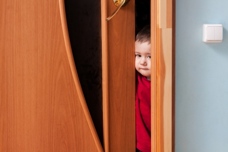 A little boy opened the door and looks into the room photo