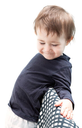downcast: Child shy and smiling with downcast eyes, leaning on wilted Stock Photo