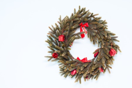 Artificial green Christmas wreath with red ornaments on the wall Stock Photo