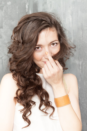 woman pose: Portrait of caucasian a girl with curly hair on a gray background