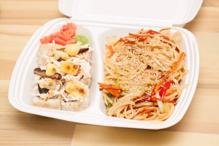chinese meal: Chinese noodles and Japanese rolls. Lunch in white container Stock Photo