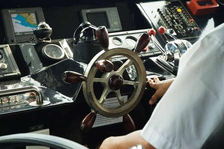 skipper: skipper piloting a boat in control room Stock Photo