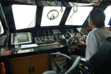 skipper: skipper sitting and piloting a boat