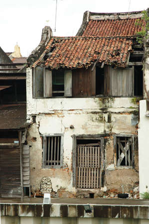 melacca: old building with wooden door and cracked wall.