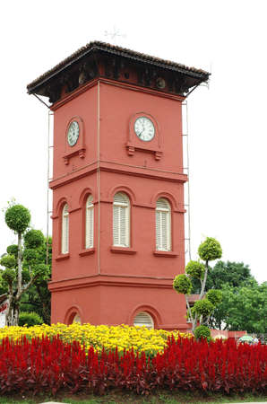 melacca: old red color clock tower in a garden