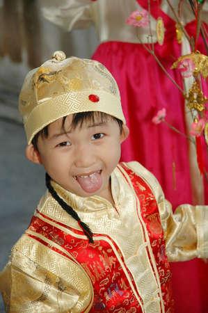 年轻的中国孩子穿着传统服装和帽子 免版税图像 - 2572325