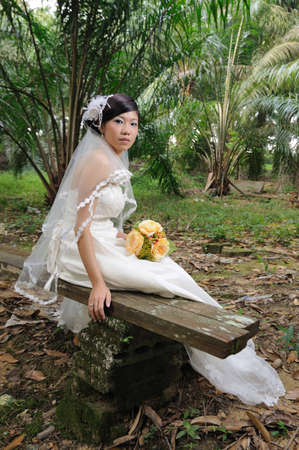 Asian bride with wooden chair in nature photo