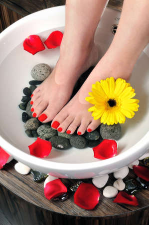 foot spa with flowers in water as background photo