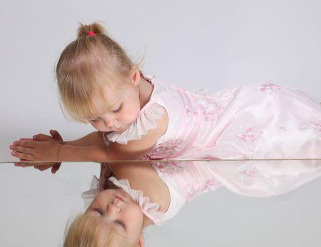 Mooie blonde meisje kijkt in de spiegel, een studio opname  Stockfoto - 5673963