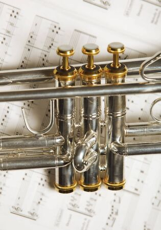 Close up part of silver B-flat trumpet on top of music sheet photo