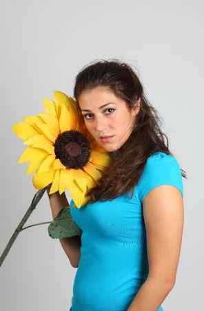 A beautiful girl with sunflower, studio shot photo