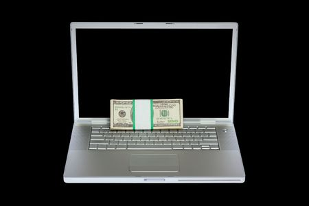Laptop and US money on isolated black background with clear keyboard photo