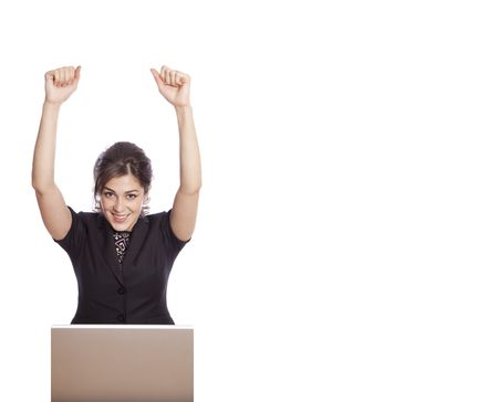 Happy businesswoman behind laptop with hands up with extra spase for text