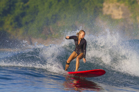 adrenaline rush: picture of girl surfing a wave in Indonesia.Lombok island.