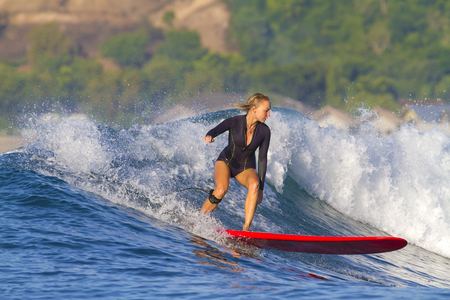 picture of girl surfing a wave in Indonesia.Lombok island.
