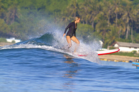 picture of girl surfing a wave in Indonesia.Lombok island. photo