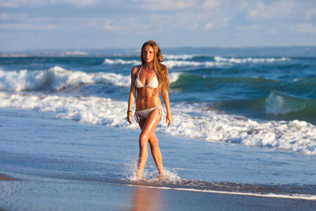 picture of the girl walking on the beach photo