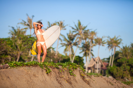 young girl with surfboard at the beach.Bali.Indonesia. photo