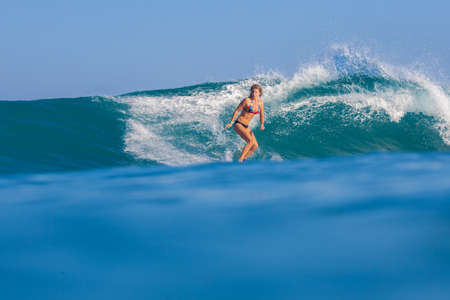 Surfer girl surfs a wave in Indian ocean. photo