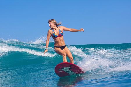 Surfer girl surfs a wave in Indian ocean.