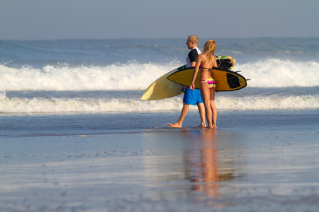 Surfer Woman and Man with Surfboards. photo