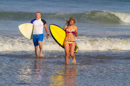 Surfer Woman and Man with Surfboards.