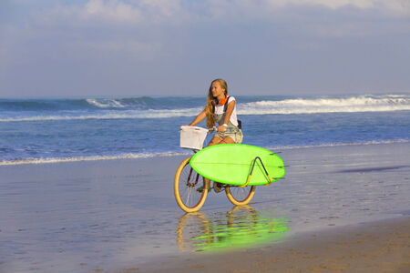 Young girl with surfboard and bicycle on the beach.