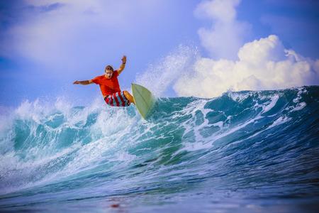 Surfer on Amazing Blue Wave, Bali island. Stock Photo