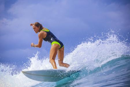 Surfer girl on Amazing Blue Wave, Bali island. Stock Photo