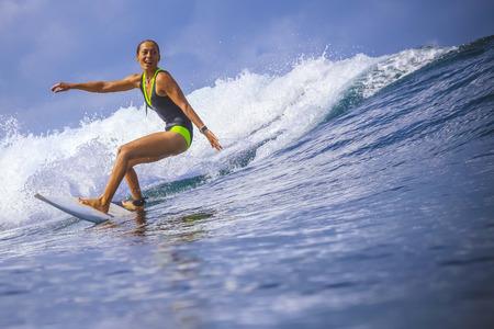 extreme weather: Surfer girl on Amazing Blue Wave, Bali island. Stock Photo
