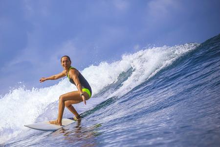 shorebreak: Surfer girl on Amazing Blue Wave, Bali island. Stock Photo