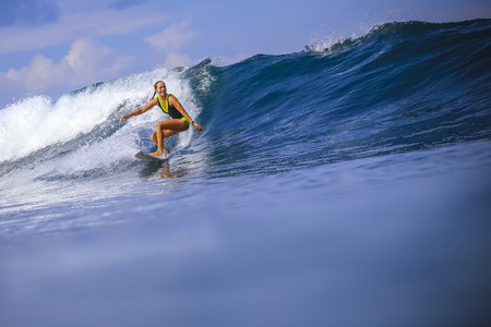 surfing: Surfer girl on Amazing Blue Wave, Bali island. Stock Photo