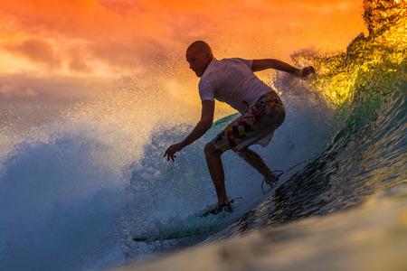 vague: Surfer Amazing vague au moment du coucher du soleil, l'île de Bali. Banque d'images