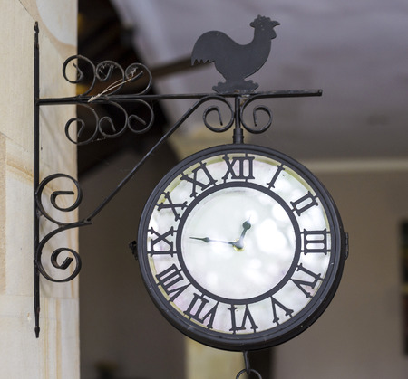 Photo of a Vintage Outdoor Chime with a Bell Hanging.