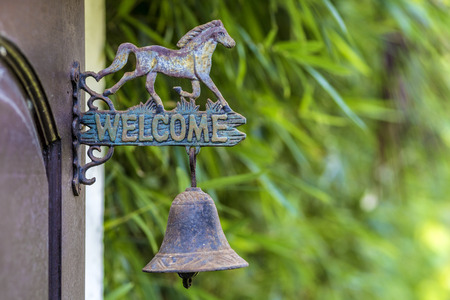 Metal sign welcome on the door with horse sculpture.