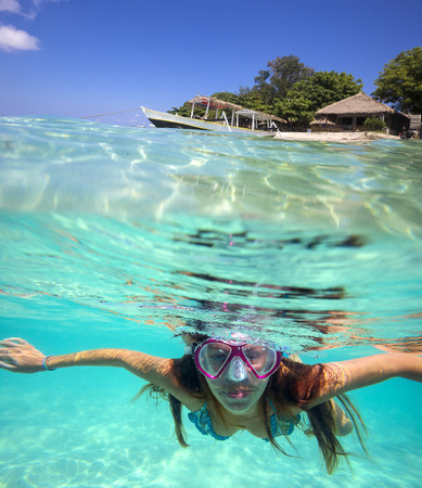 skin diving: Underwater Portrait of a Yong Woman Snorkeling in Ocean. Stock Photo