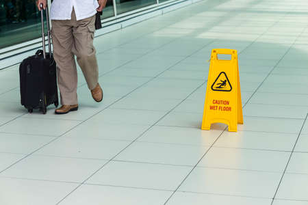 alerts: Yellow sign that alerts for wet floor in airport.