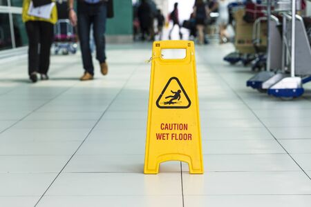 mojada: Yellow sign that alerts for wet floor in airport.
