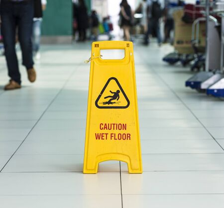 caution sign: Yellow sign that alerts for wet floor in airport.