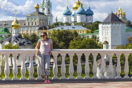 lavra: Young Woman in Sunglasses with Trinity Sergius Lavra in Sergiev Posad in background.Moscow region. Russia. released Stock Photo