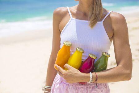 frio: Mujer joven con el jugo de vegetales crudos prensado en frío-Orgánica